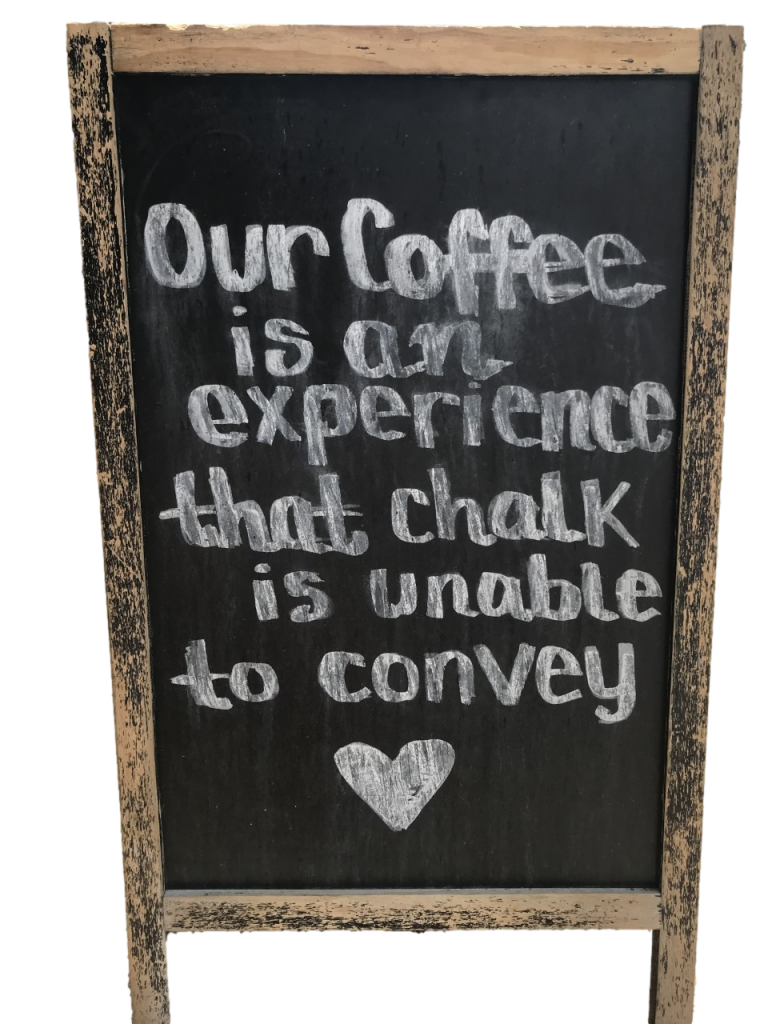 """easel with quote """"Our Coffee is an experience that chalk is unable to convey."""""""